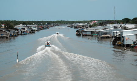 move in: Amazing scene on waterway at Mekong Delta, Vietnam. Motor boat move in fast on Ca Mau river, motorboat make wave on water, riverside residential with house make from metal sheet at Camau, Vietnam