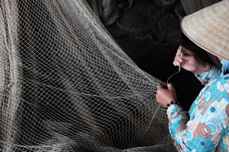 fishing village: Vietnamese woman sewing fishing net at Ca Mau fishing village, Vietnam