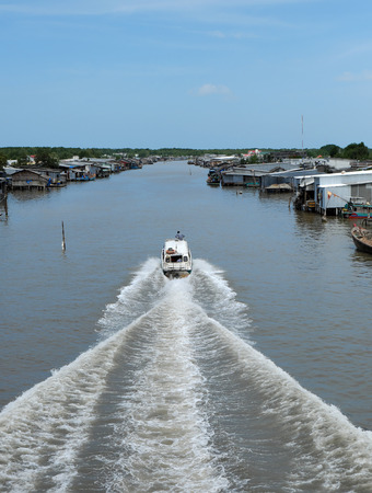 motorboat: Amazing scene on waterway at Mekong Delta, Vietnam. Motor boat move in fast on Ca Mau river, motorboat make wave on water, riverside residential with house make from metal sheet at Camau, Vietnam