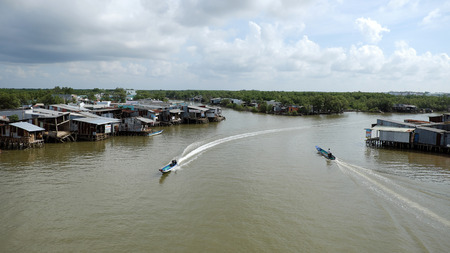 motor boat: CA MAU, VIET NAM- JULY 16, 2016:  Waterway at Mekong Delta, motor boat move on Nam Can river, poor residential with house make from metal sheet among mangrove forest, Camau, Vietnam