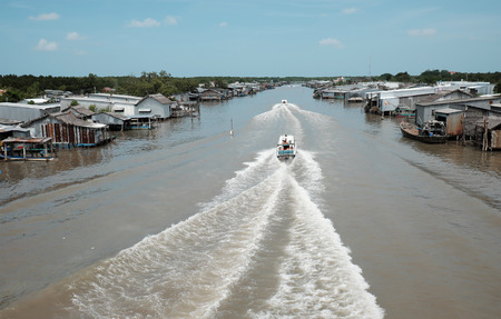 motor boat: Amazing scene on waterway at Mekong Delta, Vietnam. Motor boat move in fast on Ca Mau river, motorboat make wave on water, riverside residential with house make from metal sheet at Camau, Vietnam