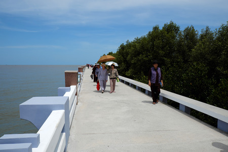 CA MAU, VIET NAM- JULY 16, 2016: Group of tourist travelling Dat Mui, a geography place people walking on breakwater along the beach Editorial