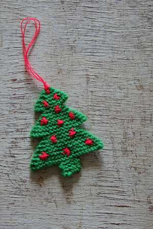 Knitted xmas tree on wooden background, Christmas trees knit from green yarn for holiday season Archivio Fotografico