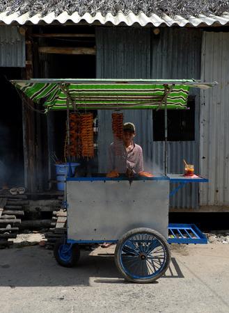 street vendor: HO CHI MINH CITY, VIET NAM- JULY 16: Vietnamese man roast quail meat on street for sale, street vendor with popular street food, delicious roasted quails