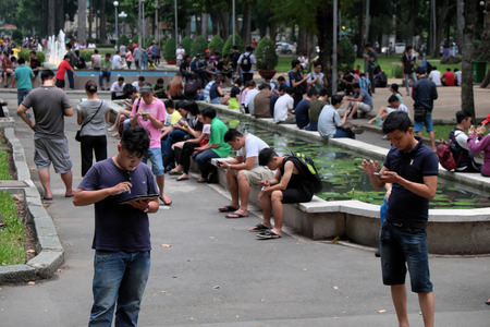 HO CHI MINH CITY, VIET NAM- AUG 20: Group of Vietnamese gamer at Tao Dan park to play Pokemon go game on smart phone, hot virtual game for modern entertainment in technology life, danger for society