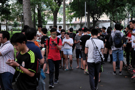 HO CHI MINH CITY, VIET NAM- AUG 20: Group of Asian gamer at Tao Dan park to play Pokemon go game on smart phone, hot virtual game for modern entertainment in technology life, danger for society Stock Photo - 61913428
