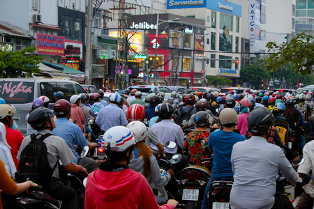 HO CHI MINH CITY, VIET NAM- AUG 24: Crowded scene at Asian city in rush hour, group of traffic vehicle as motorbike, car stop at traffic light in stress situation Imagens - 61913439