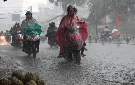 HO CHI MINH CITY, VIET NAM- AUG 28, 2016: Group of Vietnamese people wear helmet and raincoat ride motorbike in heavy rain, water on street, this time is rainy season at Saigon, Vietnam