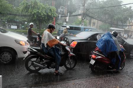 heavy rain: HO CHI MINH CITY, VIET NAM- AUG 28, 2016: Group of Vietnamese people wear helmet and raincoat ride motorbike in heavy rain, water on street, this time is rainy season at Saigon, Vietnam