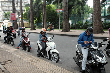 HO CHI MINH CITY, VIET NAM- AUG 28: Vietnamese people stop motorbike at roadway to play pokemon go, a hot game on smart phone, gamer staring at phone when sit on motorcycle near Tao Dan park, Vietnam 新聞圖片
