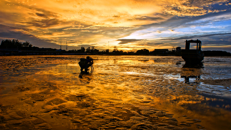 Silhouette of Asian photographer take photo with nature background, vibrant yellow of sky in sunset, wonderful landscape for Vietnam travel, tide going out at sea