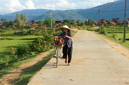 BINH DINH, VIET NAM- AUG 22, 2015: Vietnamese old woman ride bicycle on countryside road near brick kiln, the female very healthy by active lifestyle, Vietnam