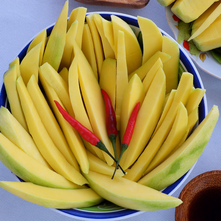 absorption: Vietnamese fruit, green mango cut in slice, a popular tropical fruit, rich vitamin A, vitamin C, collagen, good for health and impulse calcium absorption Stock Photo