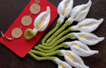 Amazing happy new year background from wood banner with nine of handmade white arum lily knit from yarn, diy home decor to make new year ornament in spring