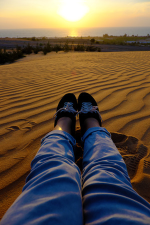 Summertime background with woman foot on sand hill, people relax on orange sandy under blue sky at Mui Ne, Phan Thiet, Vietnam, summer is coming and a trip to adventure make awesome life