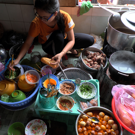 MUI NE, VIET NAM- JAN 22, 2017: Vietnamese woman sell Vietnam food for breskfast, rice spagheti and banh mi in small restaurant, soup with fried fish, bread with braised pork, material show on floor