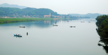 landscaping riverside: Amazing natural landscape at Quang Binh, Viet Nam on day, boat moving on river,  riverside house with mountains behind, green field beside water, beautiful scene for Vietnam travel