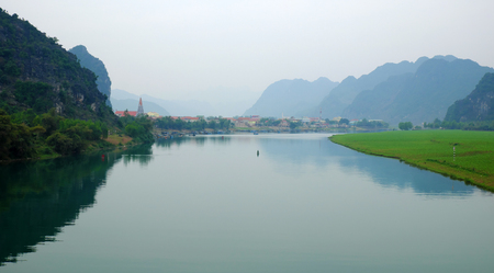 riverside landscaping: Amazing natural landscape at Quang Binh, Viet Nam on day, boat moving on river,  riverside house with mountains behind, green field beside water, beautiful scene for Vietnam travel