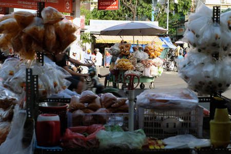 HO CHI MINH CITY, VIET NAM- MARCH 18, 2017: Vietnamese street food at Cho Lon market, street vendor earn money with many kind of rice paper in push carts, popular snacks food in Vietnam