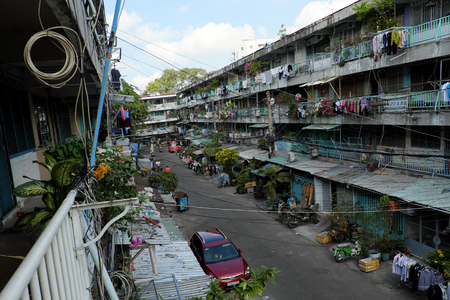 downgrade: HO CHI MINH CITY, VIET NAM- APRIL 20, 2017: Overview of old apartment building in downgrade stage on day, block of flat with interlaced electric wire at Vietnam