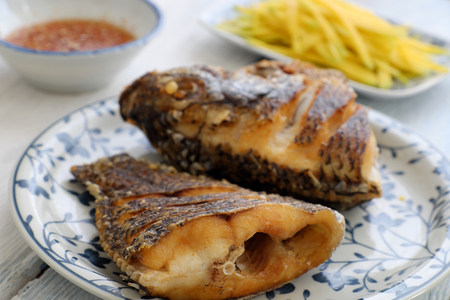 Vietnamese food for daily meal, fried fish with mango and fish sauce, titapia fish or saint peter fish fry is delicious eating Stock Photo