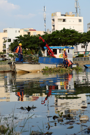 HO CHI MINH CITY, VIET NAM- APRIL 27, 2017: Sanitation worker working on boat to picking up trash from water on day, many rubbish on water surface make pollution water, Vietnam