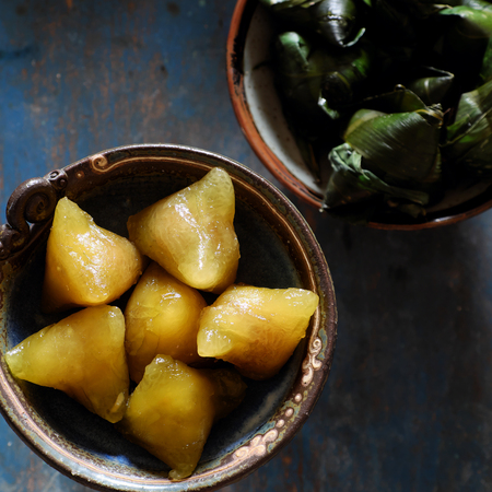 Vietnamese traditional food for may 5th, is double five festival or tet doan ngo, sticky rice cake in green leaf, also call banh u tro with pyramidal shape Banco de Imagens