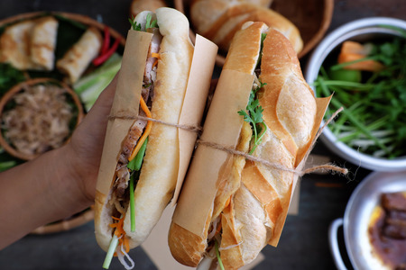 Woman hand make banh mi thit or Vietnamese bread, famous street food from  raw material: pork, ham, pate, egg and fresh herbs as scallions, coriander, carrot, cucumber, chilli. Stock Photo - 79586293