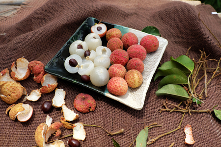 Close up plate of fruit on brown background, litchi or lychee fruits or Vai thieu. Red fruit peel with juicy pulp in white that sweet and delicious