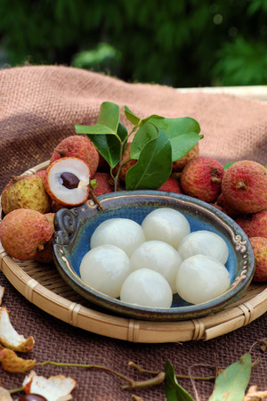 ha giang: Close up of litchi fruit or lychee fruits, a tropical agriculture product at Luc Ngan, Bac Giang, Vietnam, basket of Vai thieu on brown background Stock Photo