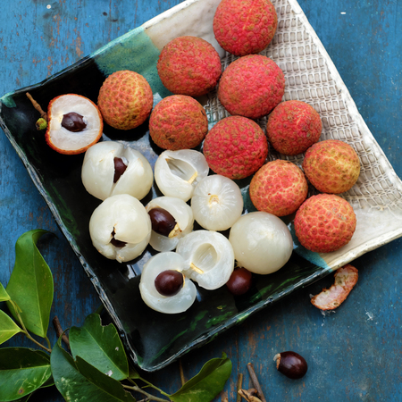 Close up plate of fruit on blue background, litchi or lychee fruits or Vai thieu. Red fruit peel with juicy pulp in white that sweet and delicious