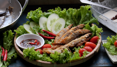 Vietnamese food for family meal at lunch or dinner, fried fish with tamarind sauce and green vegetable, delicious food homemade on wooden background