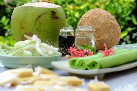 Grupo de productos de coco con caramelo, papel de arroz con leche, aceite de coco, salsa de soja oscura, mermelada o agua de coco, son alimentos populares de Vietnam, grupo de bocadillos y bebida sobre fondo verde Foto de archivo