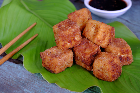 Frugal vegetarian food from Vietnamese cuisine, fried tofu with spice power, cover with crispy flour, homemade food on green leaf background, soya sauce for vegan Stock Photo