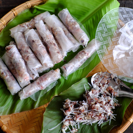 Doing Vietnamese egg roll or spring rolls or cha gio, is popular food at Vietnam cuisine, stuffing from meat and wrapper by rice paper Stock Photo