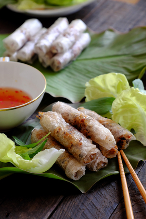 Vietnamese egg roll or spring roll or cha gio is popular food at Vietnam cuisine, stuffing from meat and wrapper by rice paper, then deep fried, eat with salad and fish sauce Stock Photo