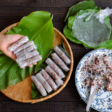 Woman making spring rolls or cha gio at home, homemade food stuffing from meat and wrapper by rice paper, hand rolling Vietnamese egg roll on green leaf background