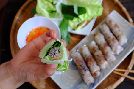Eating spring roll pastry or cha gio is popular food at Vietnam cuisine, stuffing from meat and wrapper by rice paper, then deep fried, eat with salad and fish sauce