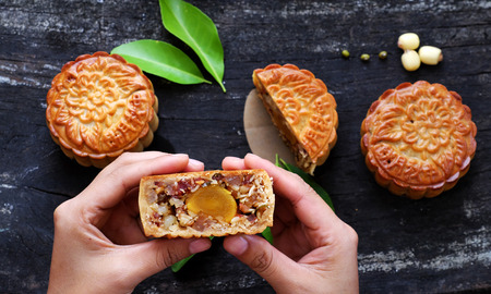 Close up of Vietnamese sweet food from top view, woman hand take moon cake for mid autumn festival when full moon, delicious homemade mooncake of Vietnam cuisine culture