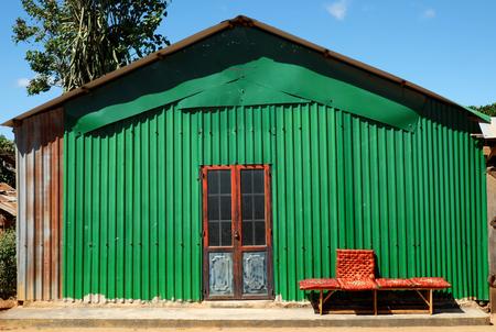 鉄の壁を持つ抽象的なファサードの家、グリーンメタルシートは家の前でロックとベンチに家、ベンチレッドドアの素敵な外観を作ります 写真素材 - 88916413