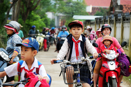 BINH DINH, VIET NAM- NOV 3, 2017:Group of Asian children coming home from school by bicycle, crowd Vietnamese pupil ride bike on country road, Vietnam 報道画像