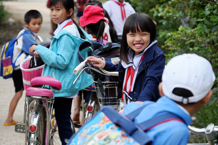 BINH DINH, VIET NAM- NOV 3, 2017: Portrait of Asian pupil after school on bicycle, at Vietnamese countryside, children ride bike to go to school