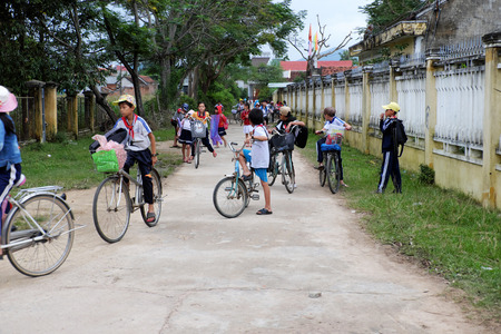 BINH DINH, VIET NAM- NOV 3, 2017:Group of Asian children coming home from school by bicycle, crowd Vietnamese pupil ride bike on country road, Vietnam Editorial