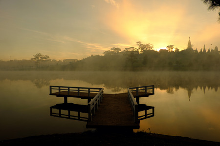 Destination for Vietnam travel at Da Lat city, mist evaporate from surface water of lake, silhouette of small bridge reflect on pond, nice at sunrise 写真素材