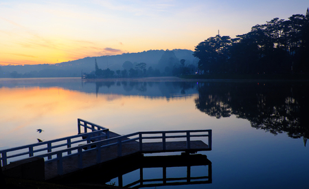 Destination for Vietnam travel at Da Lat city, mist evaporate from surface water of lake, silhouette of small bridge reflect on pond, nice at sunrise Banco de Imagens