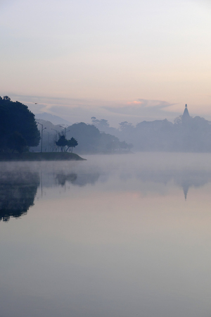 landscape of Pedagogical college of Da Lat view from Xuan Huong lake, beautiful landscape reflect on water, bell tower rise from pine forest, mist on surface water make calm scene in amazing shape at morning