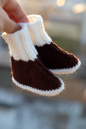 Knit baby booties for newborn from yarn, close up of cute handmade products for footwear Stockfoto
