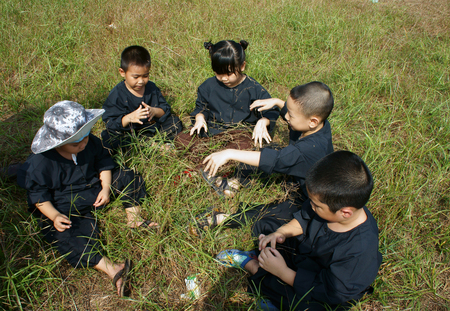 HO CHI MINH CITY, VIET NAM- JAN 14, 2014: Group of Vietnamese children in black traditional dress, sit on grassland and play together, outdoor activity make healthy lifestyle for kid, Vietnam