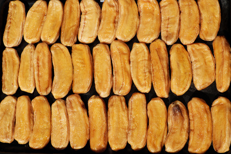 Homemade food by dry ripe banana to make dried fruits at Ho Chi Minh city, Viet Nam when hot season come, fruits tray let outdoor under high temperature to make sweet snack