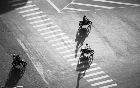 Amazing scene on street at Asian city from high view, group of Vietnamese people ride motorbikes moving with shadow on road surface make impression shape